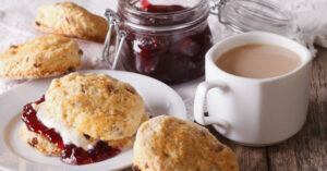 Scones with jam and tea with milk on the table.