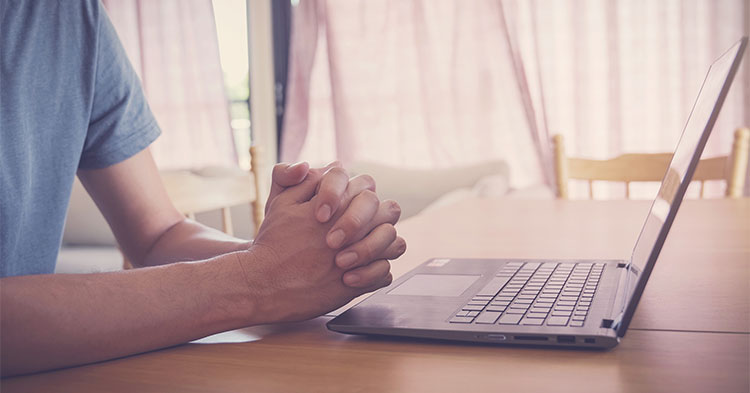Laptop and praying hands